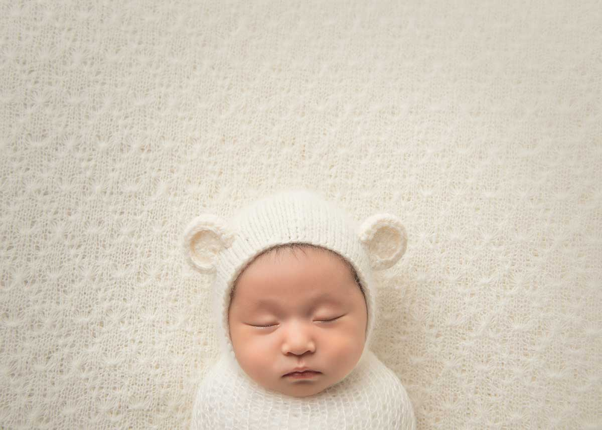 Newborn wearing a cute hat sleeping on its back