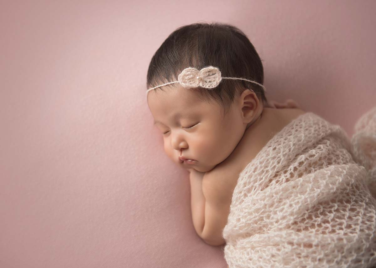 Cute newborn with black hair and headband sleeping