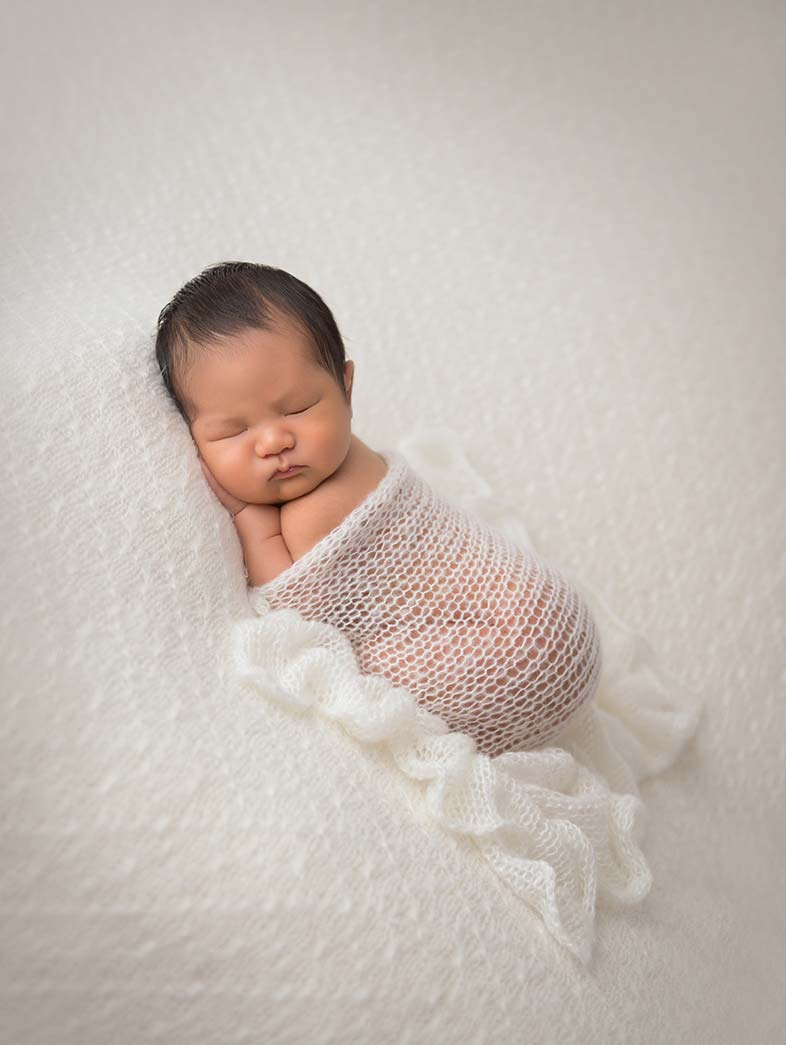 Newborn baby in a wrap sleeping at a photo studio