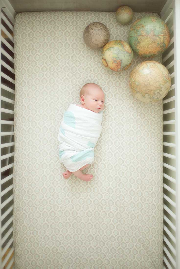Infant baby swaddled in a crib
