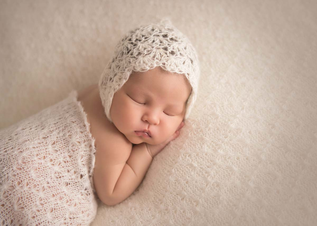 beautiful newborn on textured cream blanket with cream hat