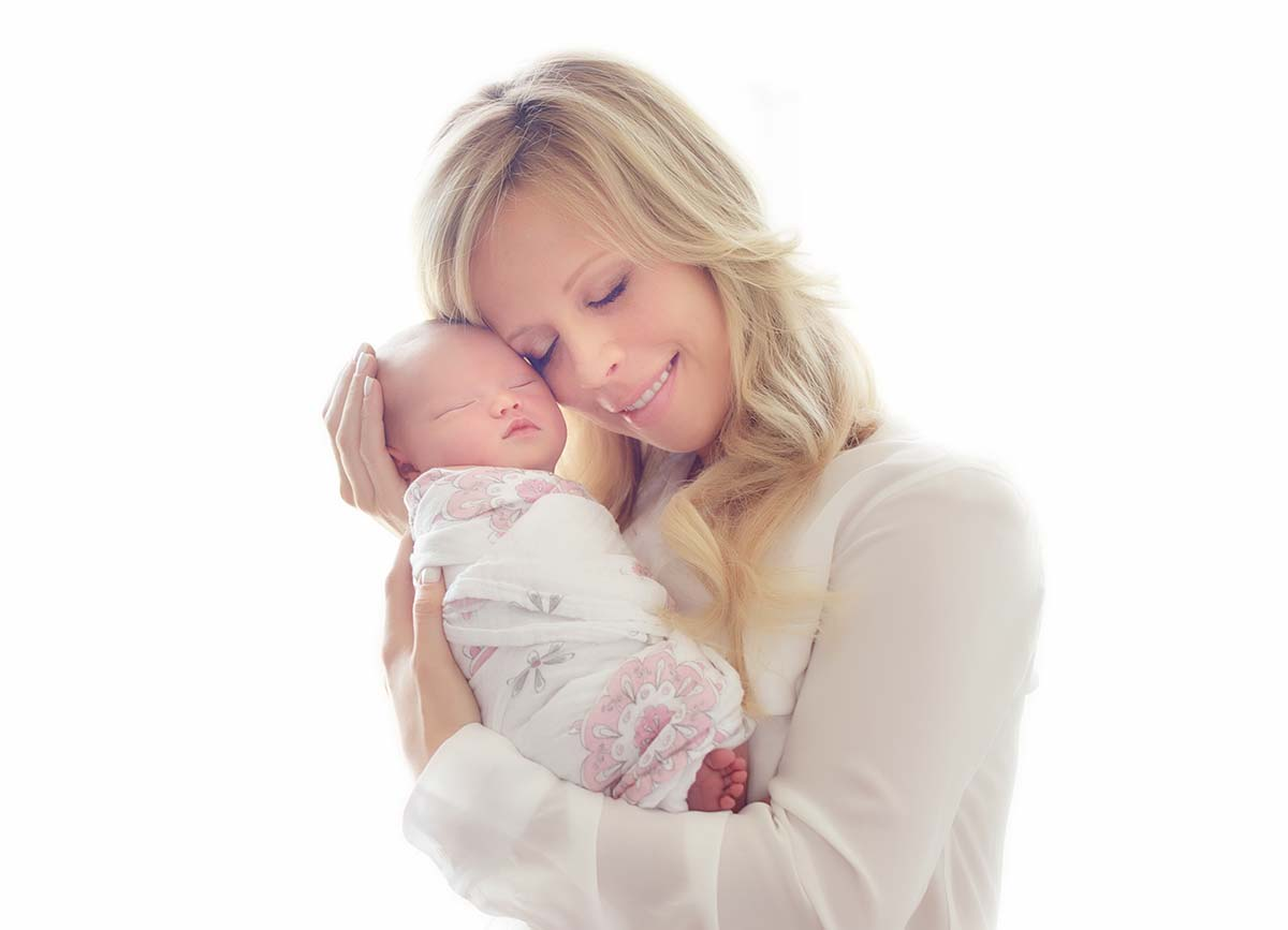 blonde mom holding infant girl swaddled in a boho wrap