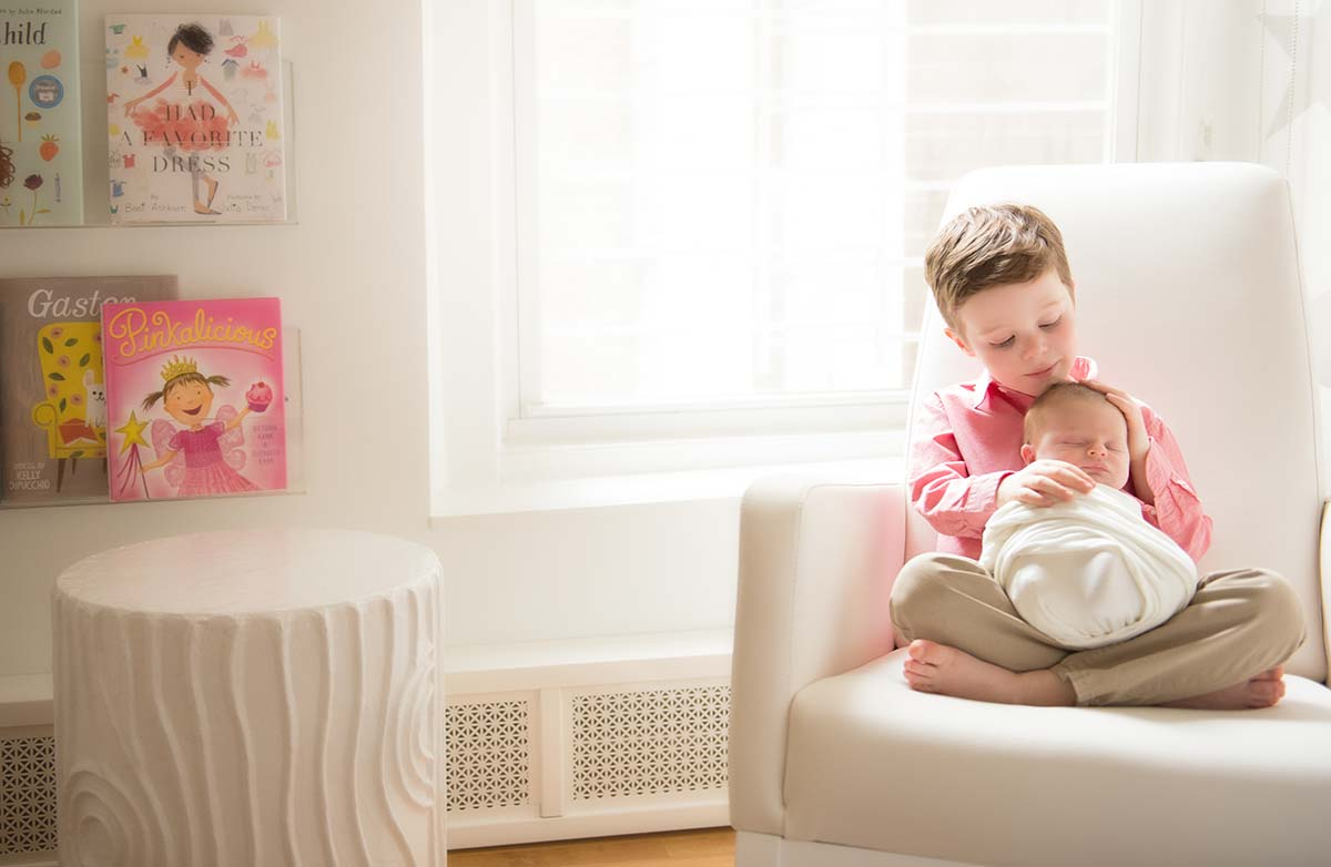 Toddler boy holding his newborn sibling on a chair