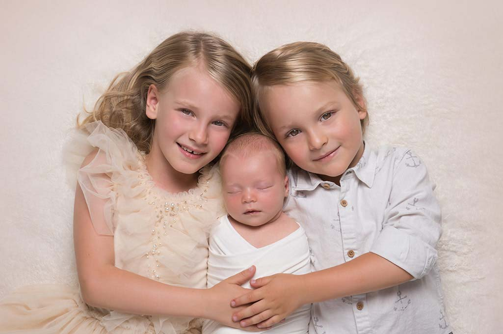 Heirloom portrait of a brother and sister holding their newborn baby sibling