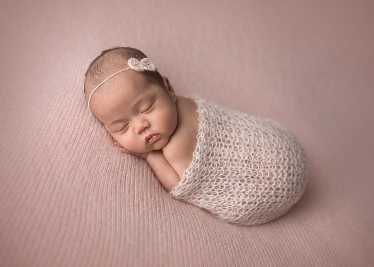 Baby with chubby cheeks sleeping during a newborn photo session