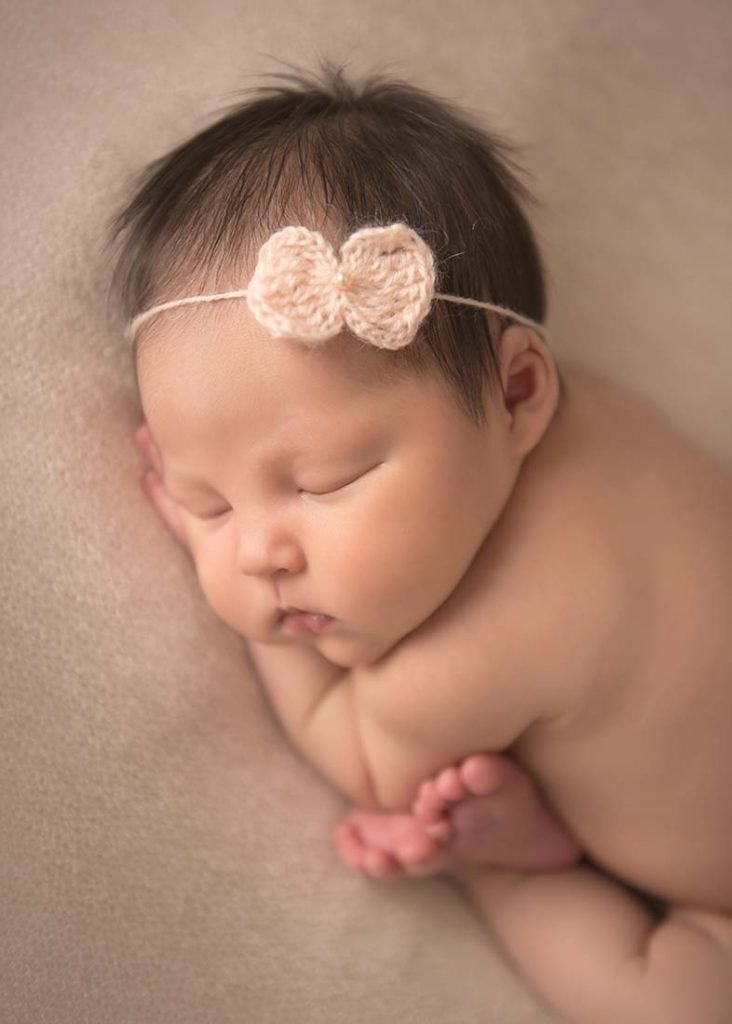 cute baby girl with peach headband in cozy newborn pose