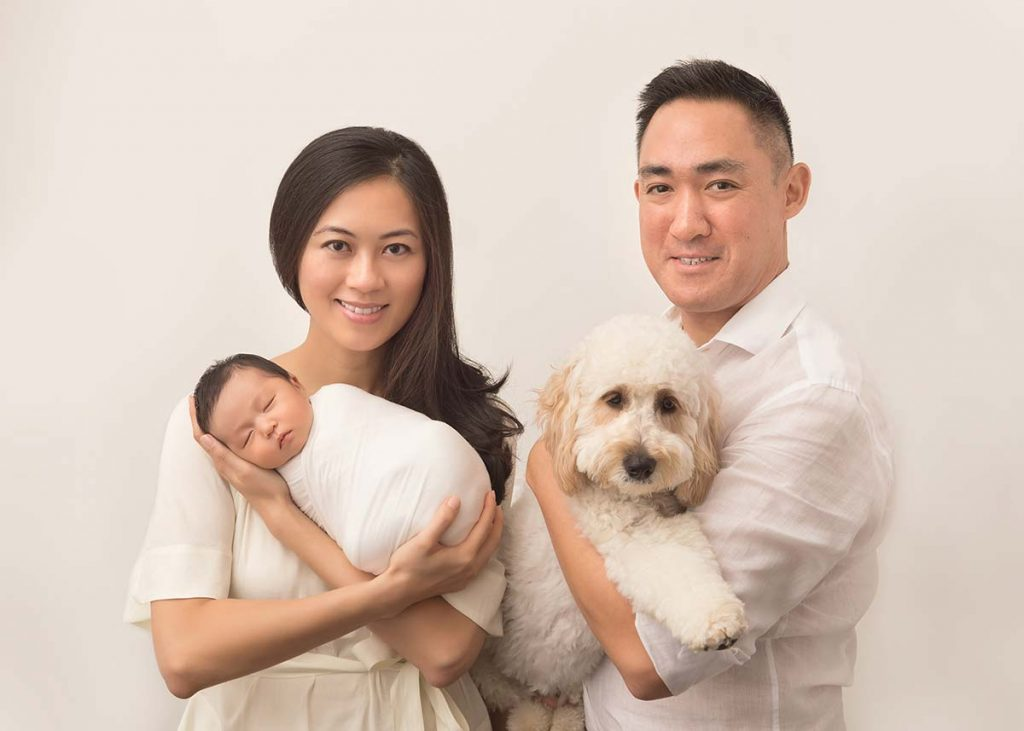Family posing with their pet and their baby