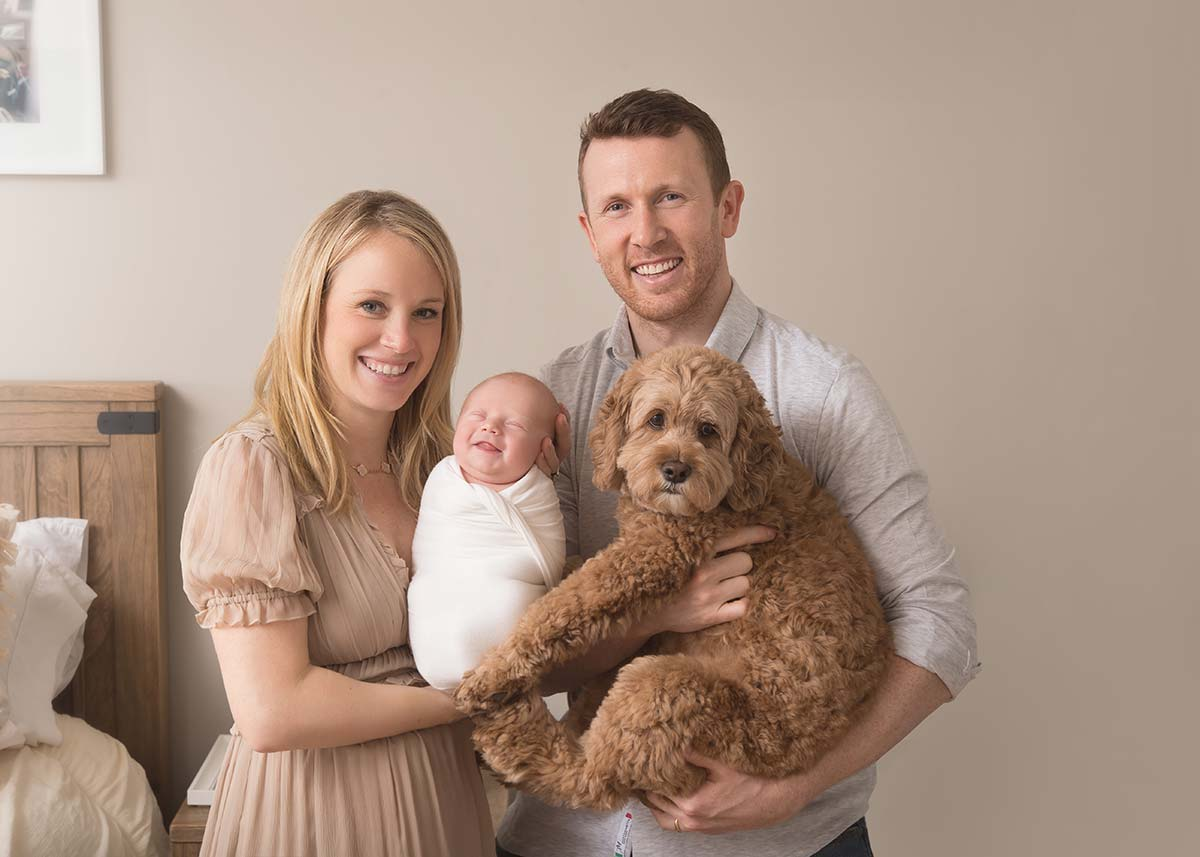 Family portrait with a smiling newborn and a pet