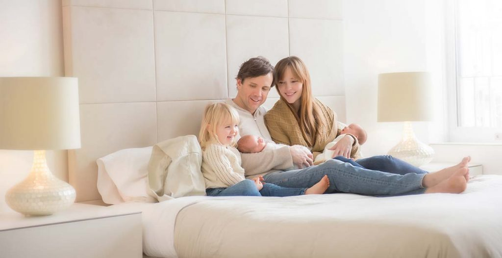 Mother holding her newborn baby on a bed along with her husband and daughter