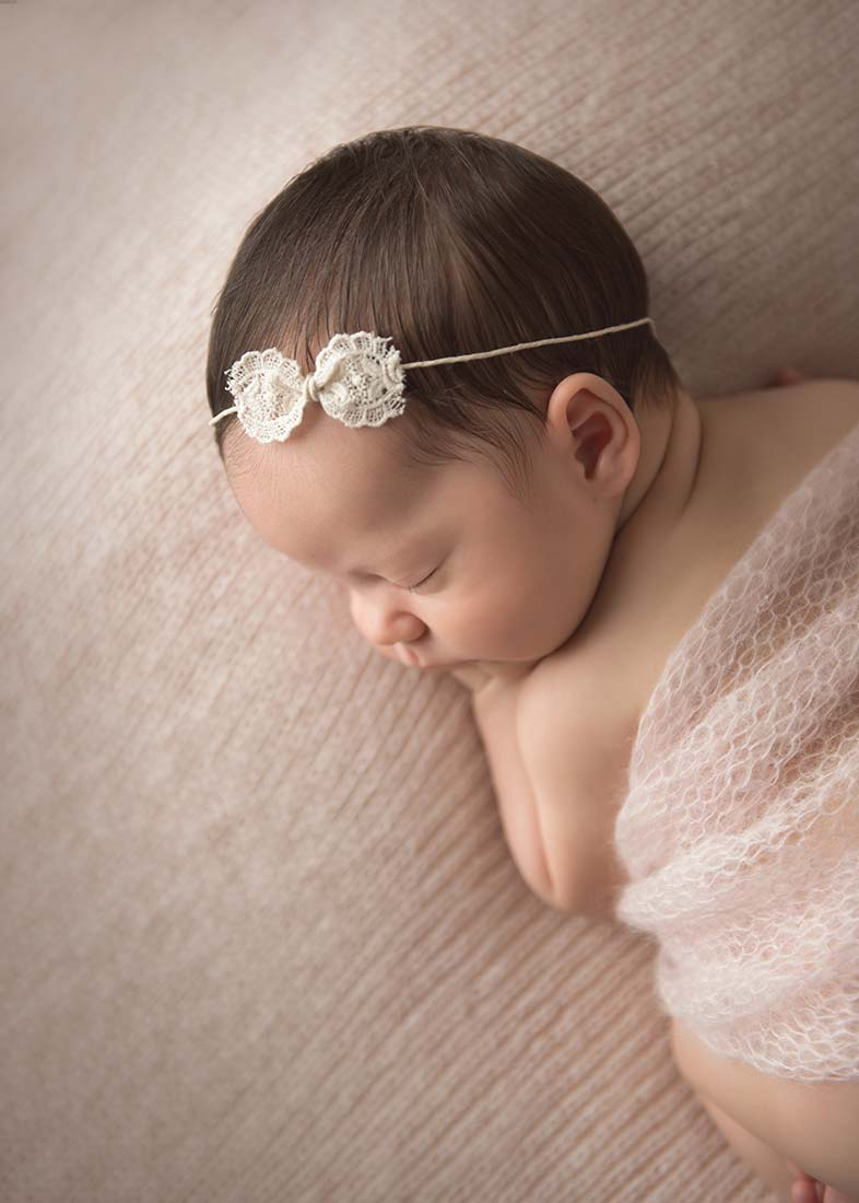 infant wearing bow headband and sleeping on wool blanket
