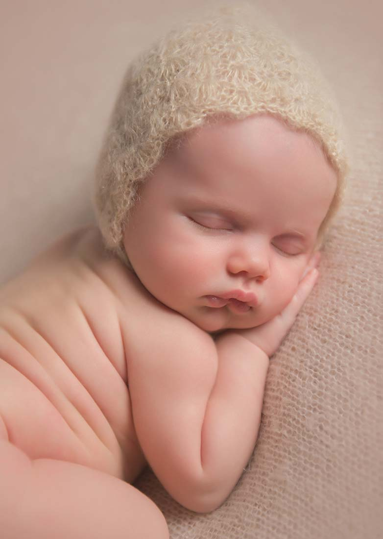 beautiful newborn girl sleeping with a crochet bonnet and pouty lips