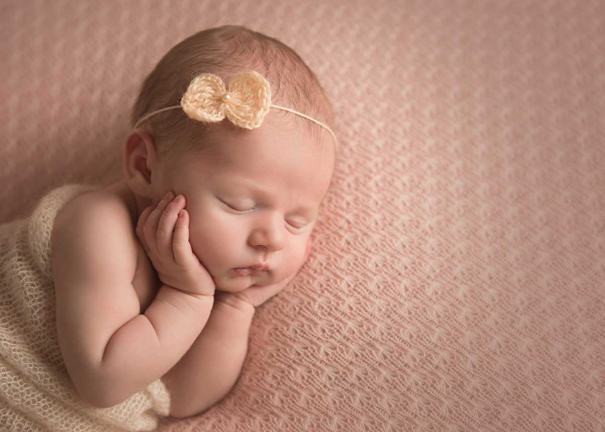 Baby girl with a headband sleeping on a knit blanket