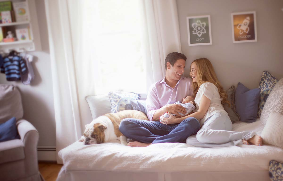 Lifestyle photo of parents sitting on bed with their baby and a dog