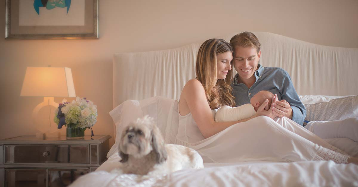 Parents sitting on the bed and cradling their baby with a puppy sitting near