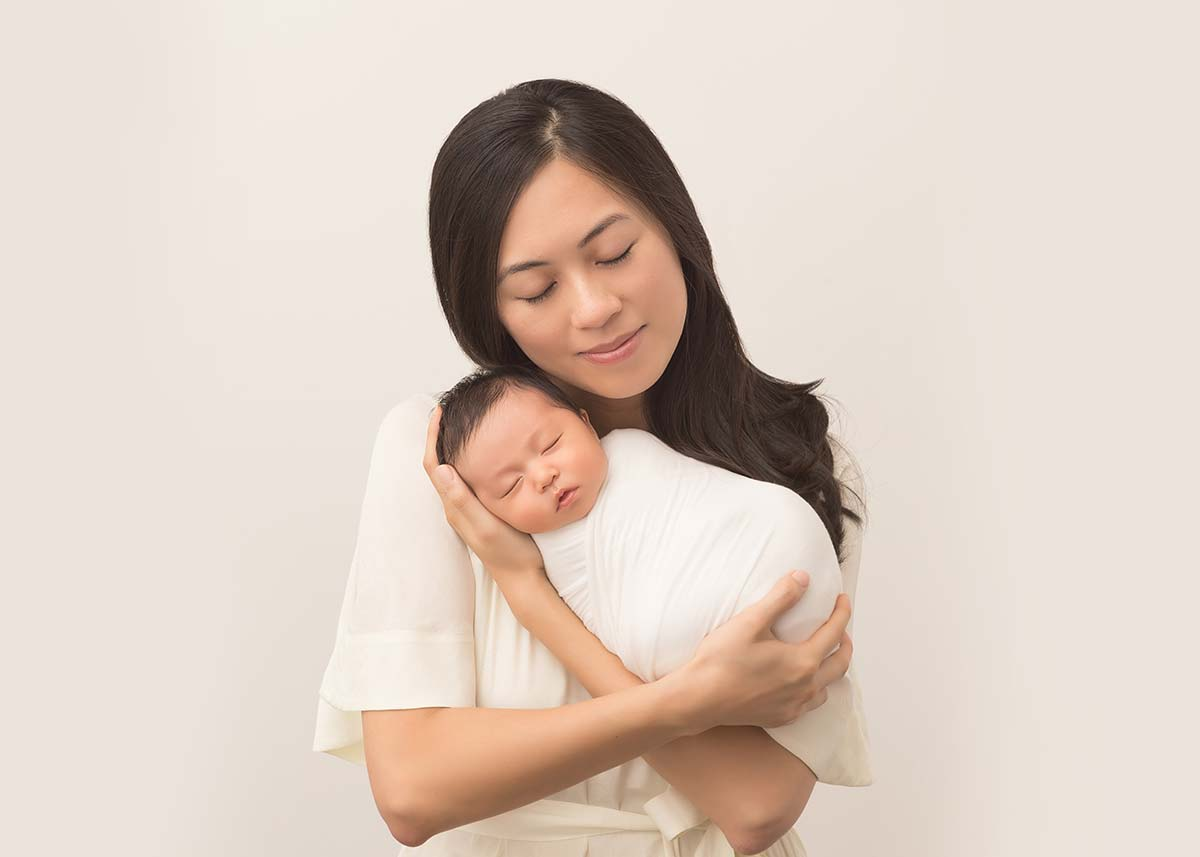 Mom holding her swaddled newborn in arms