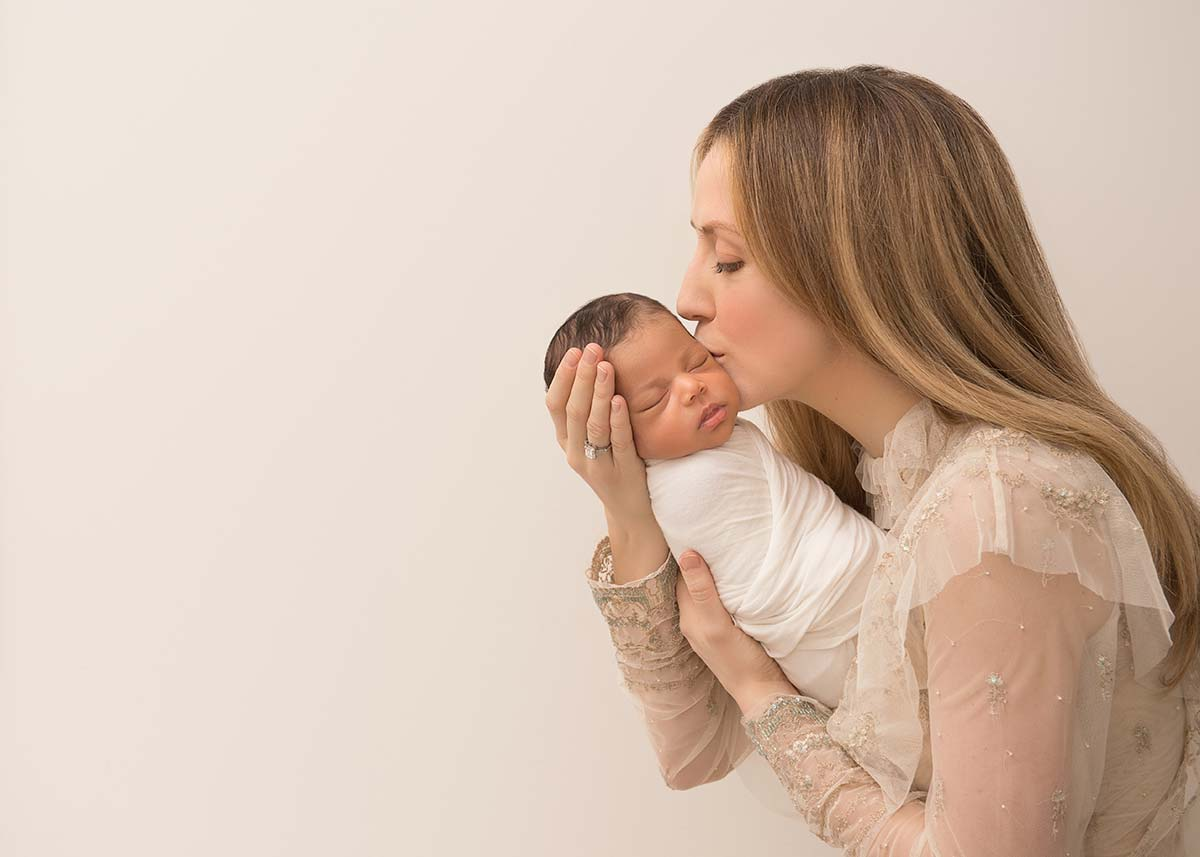 Mother kissing her infant baby on the cheeks