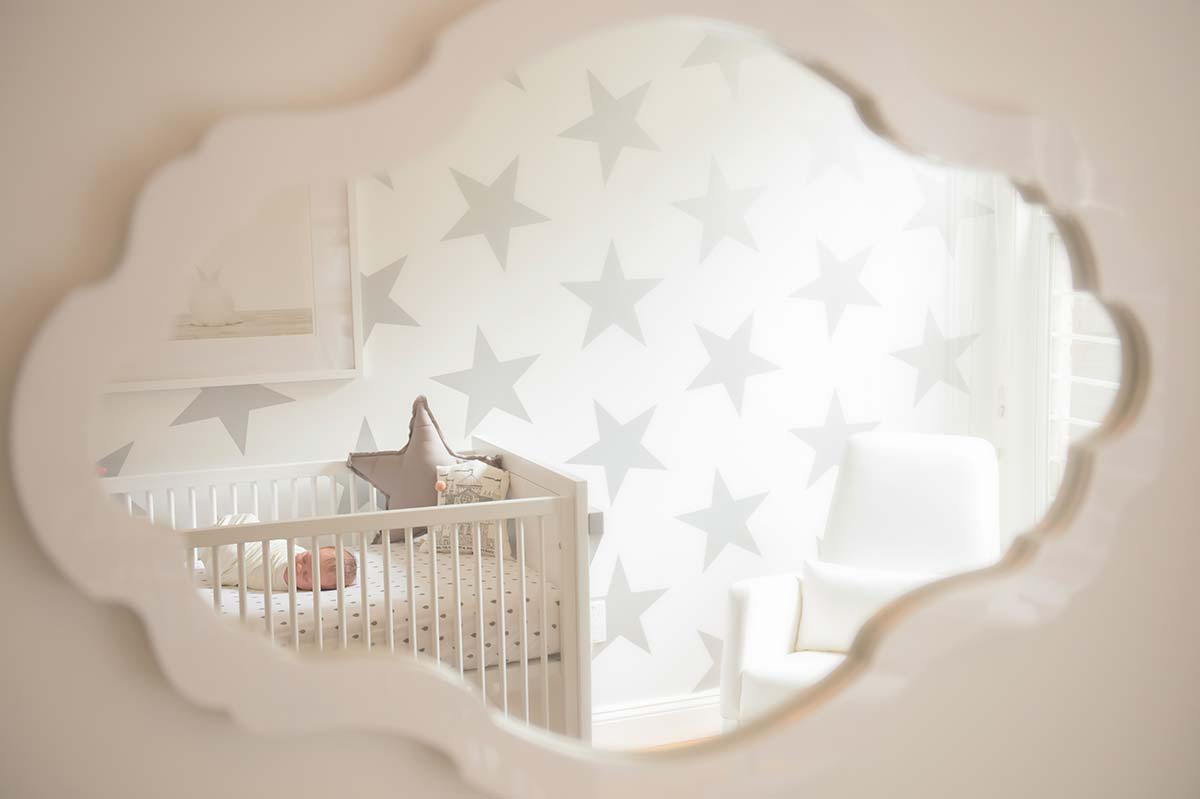 A crib with a newborn baby reflected in a nursery mirror