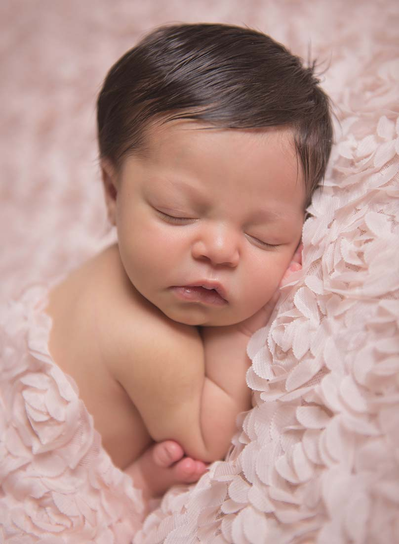 Newborn baby with black hair on a rose blanket