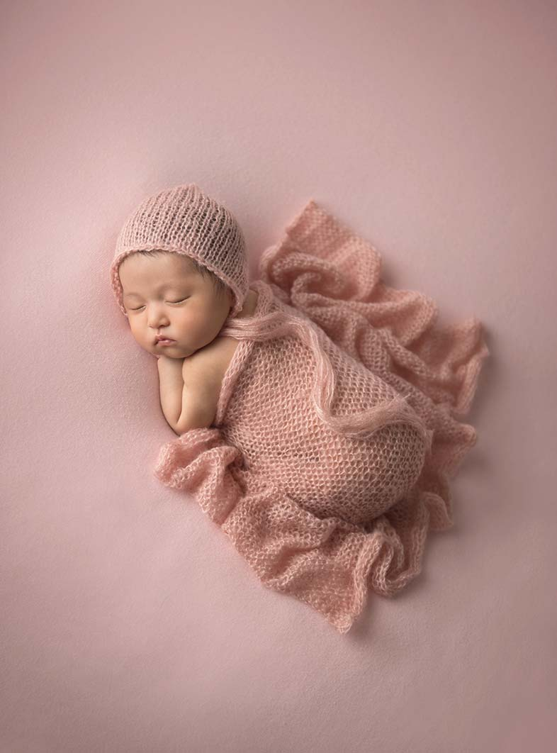 Newborn baby sleeping calmly on a pink blanket