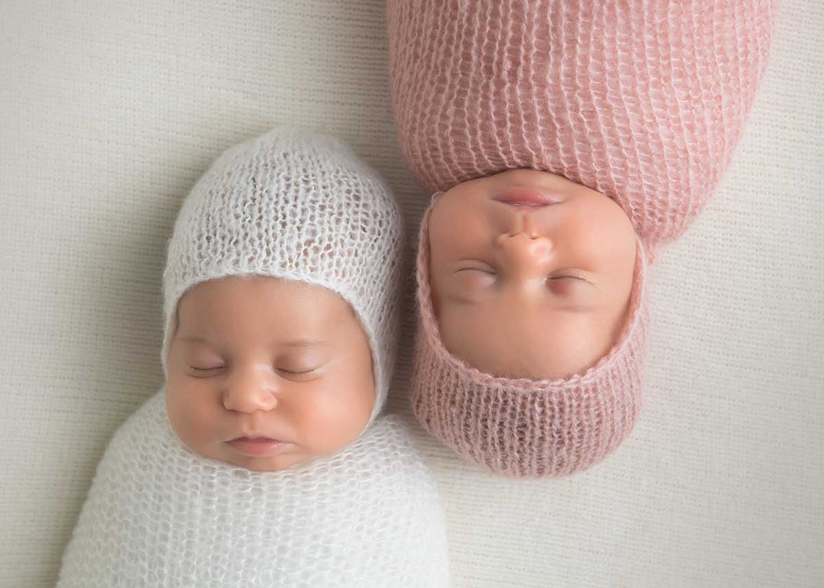 Newborn twins swaddled with hats