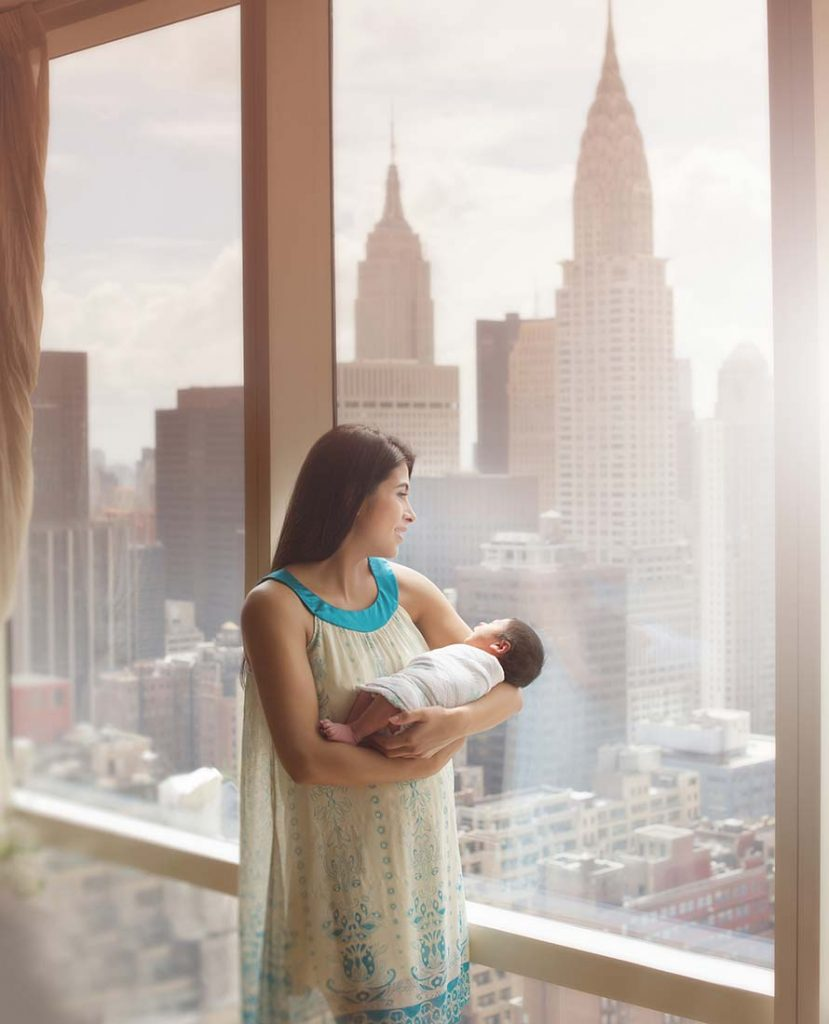Mother holding her newborn baby near a window with a beautiful view of the NYC skyline