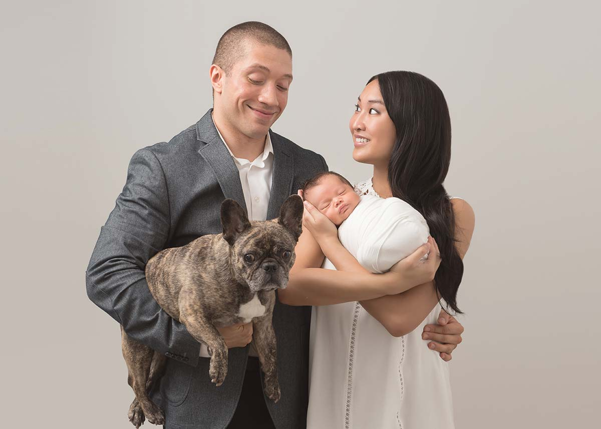 Happy married couple holding their baby and their dog while posing for a family portrait