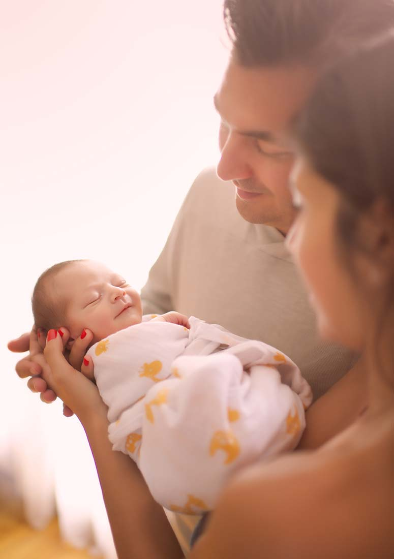 Parents holding their newborn son posing for a portrait