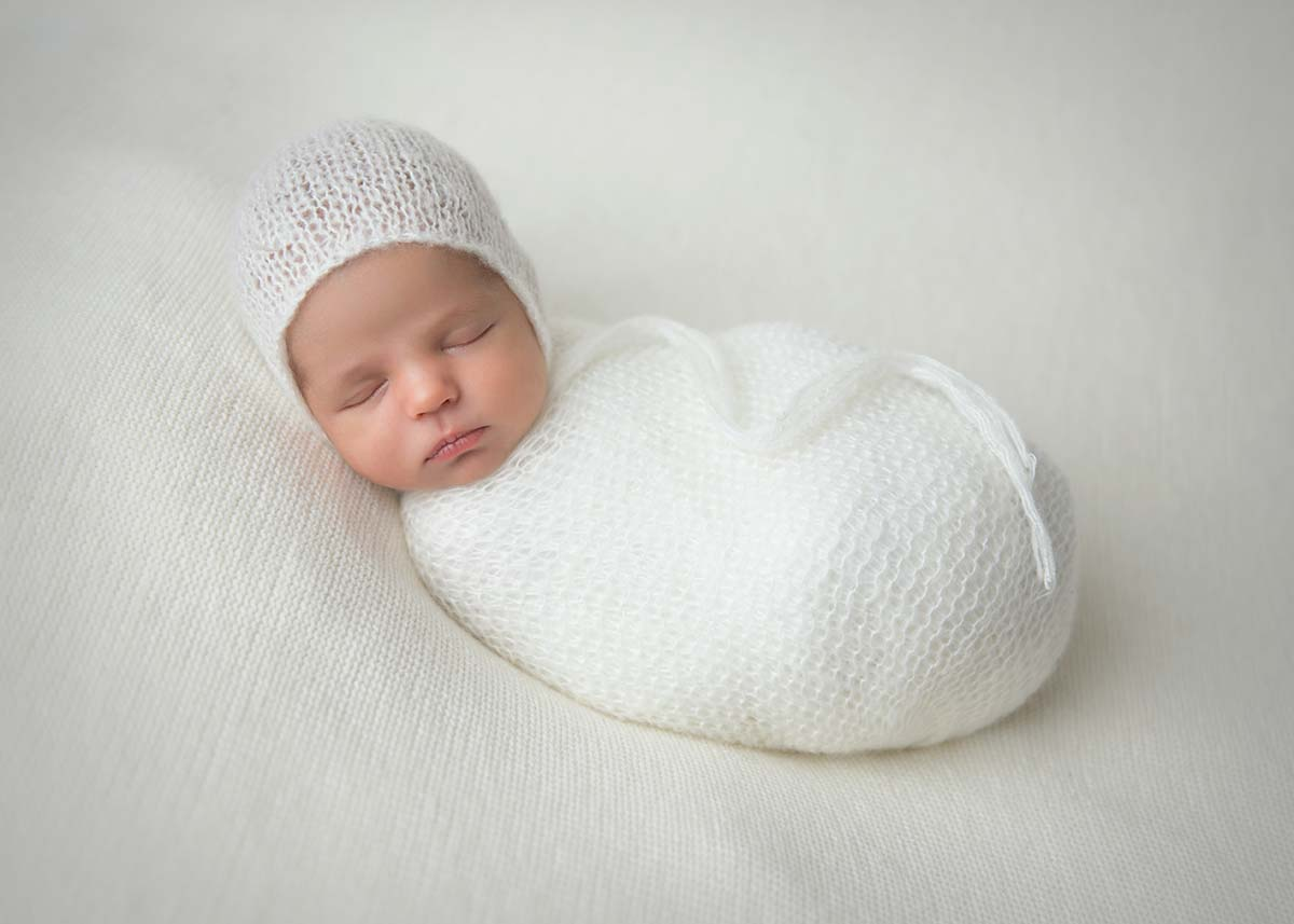 Newborn swaddled in a white wrap