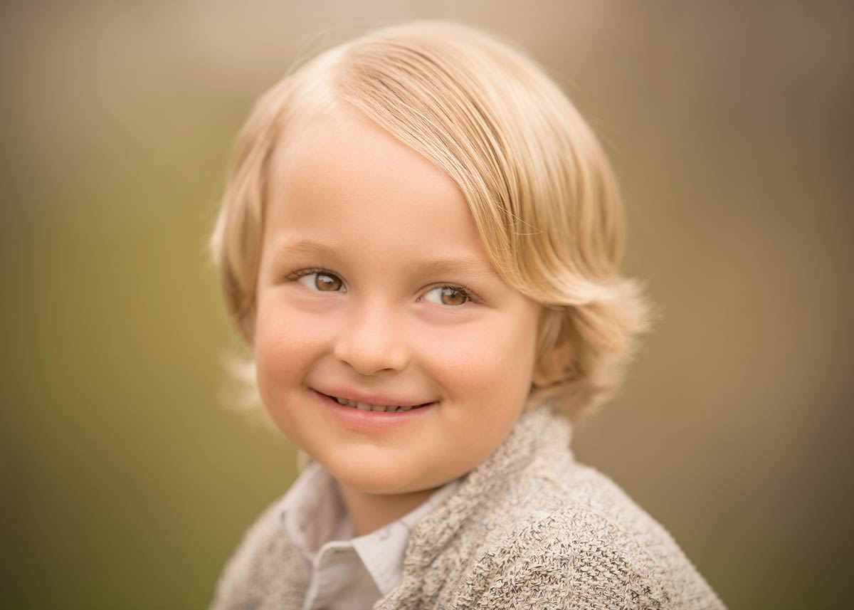 Closeup portrait of a boy with blonde hair smiling