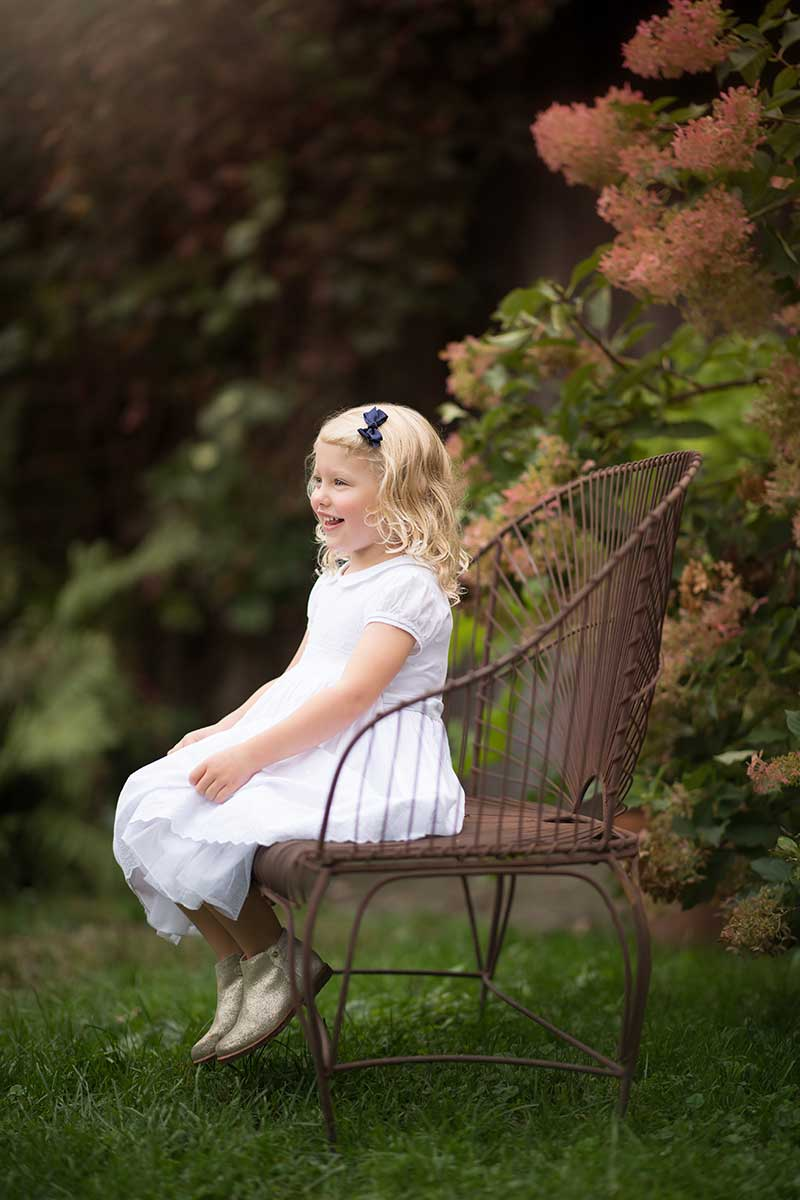Blonde girl in a white dress sitting on a bench smiling