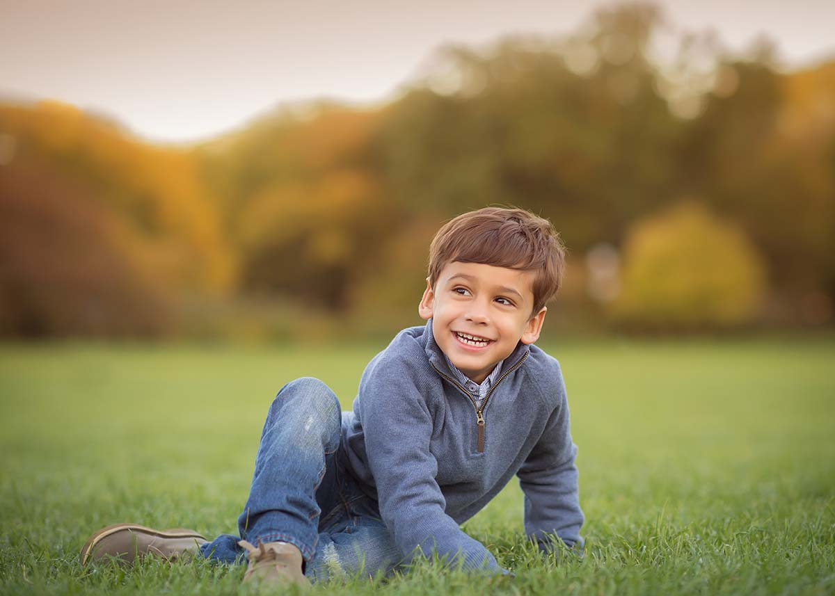 Boy in jeans smiling in grass