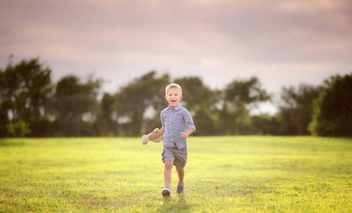 Young boy running through a grass field