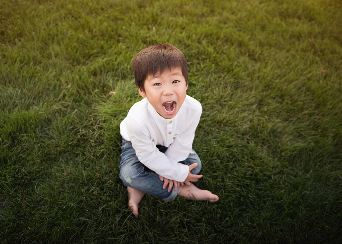 Boy smiling while sitting in grass