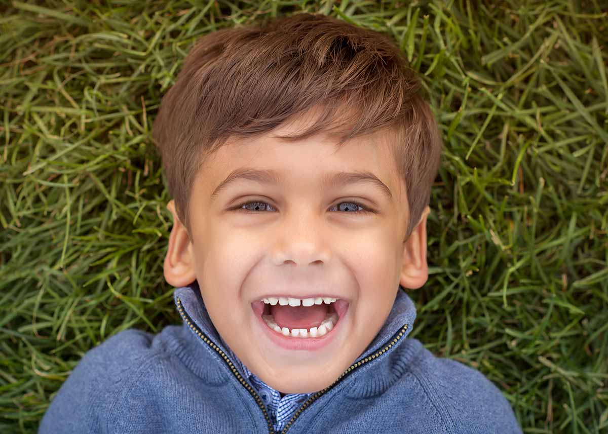 Top down view of a boy smiling in grass