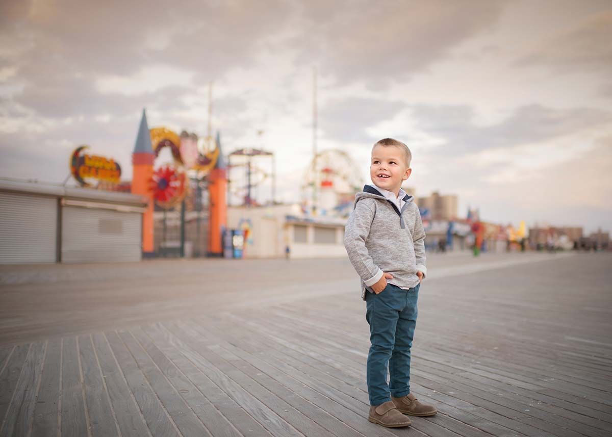 Boy standing on a pier in Coney Island, NYC