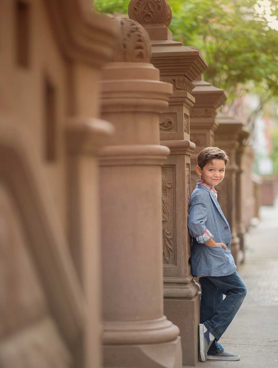 Stylish boy standing near a brownstone townhouse in NYC