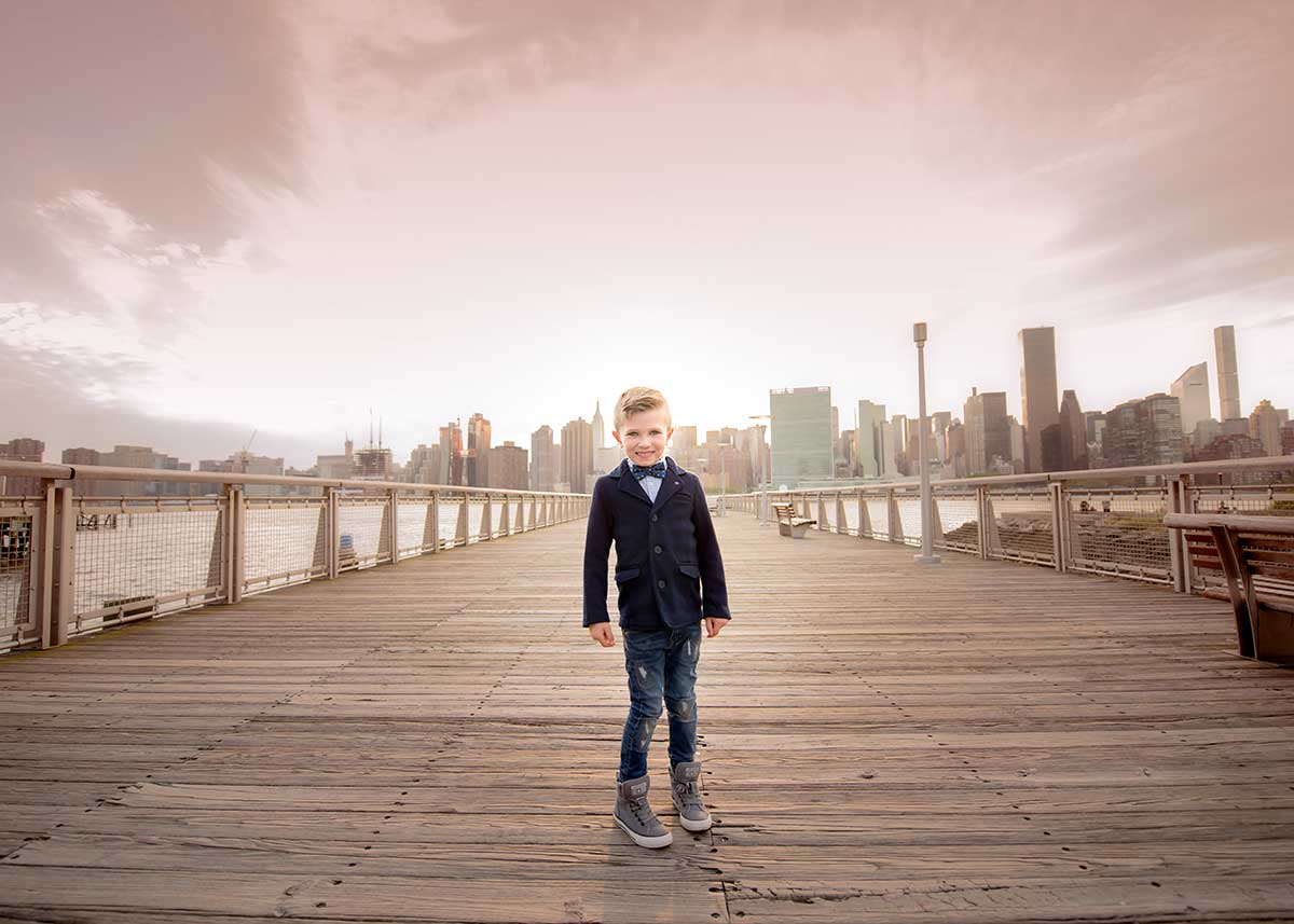 Young boy in a tuxedo standing on a pier in NYC
