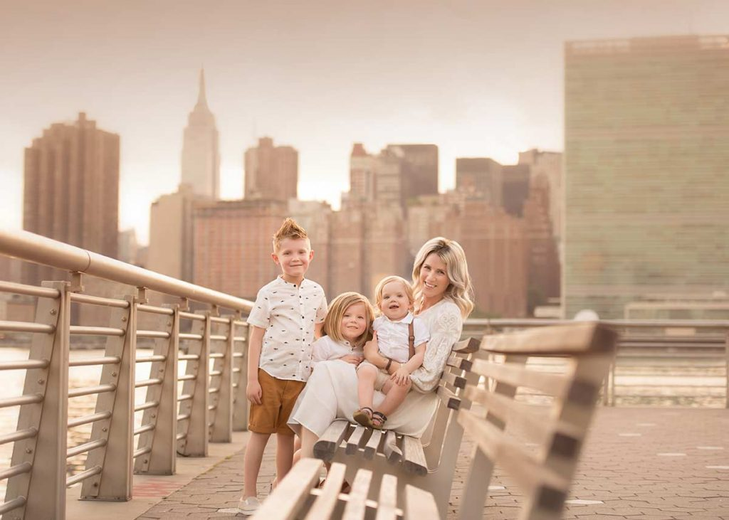 Three boys and their mother posing for a family portrait in NYC
