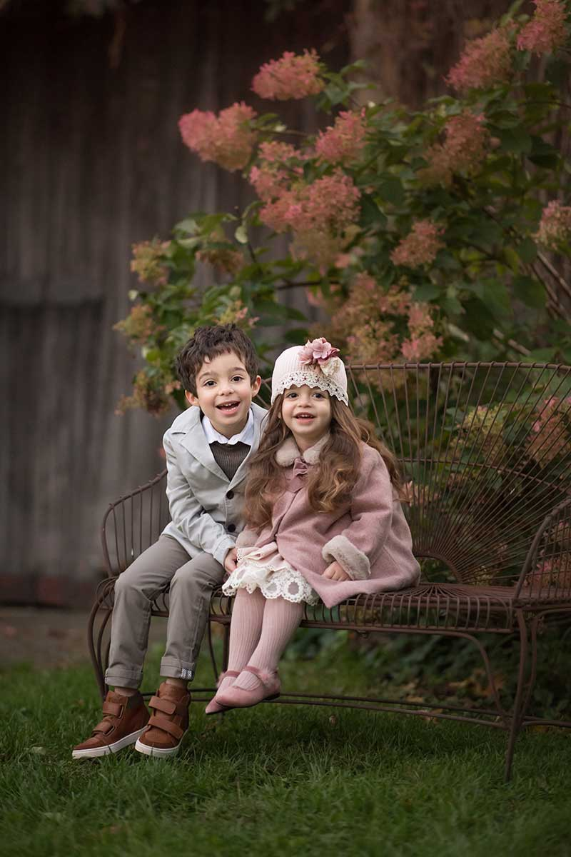 Siblings dressed in stylish clothes sitting on a bench smiling