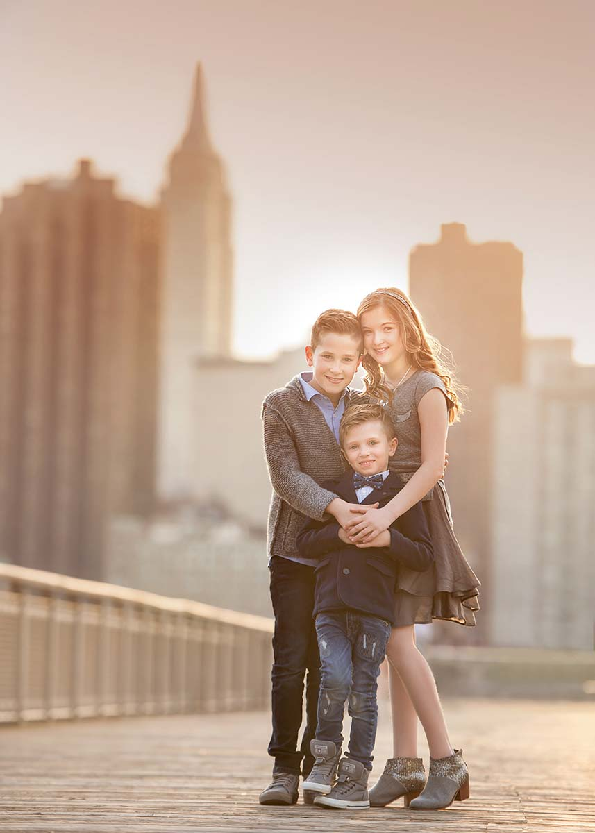 Three children posing for a beautiful portrait with Empire State Building in the background