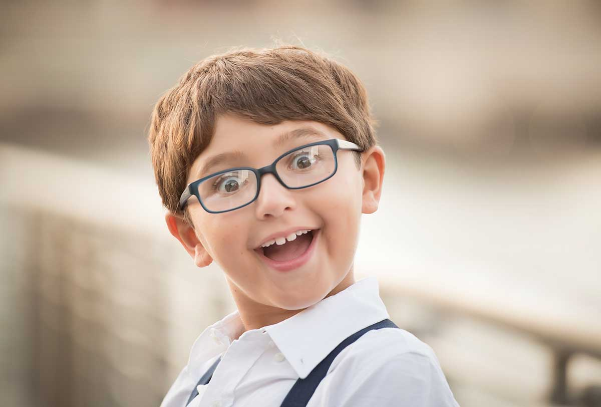 Candid portrait of a boy with glasses smiling happily