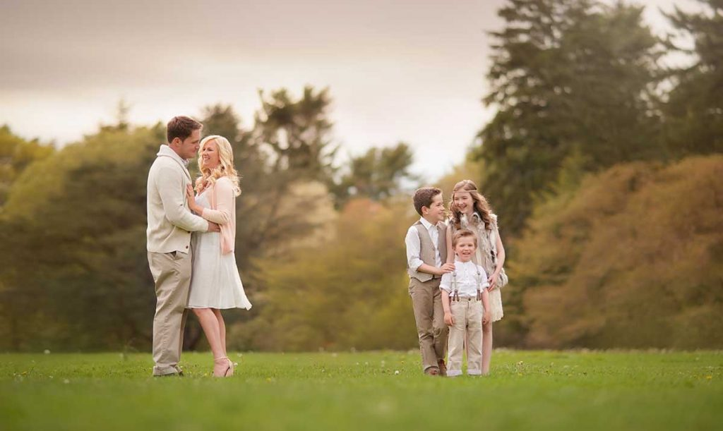Happy family moment in a park with parents and children