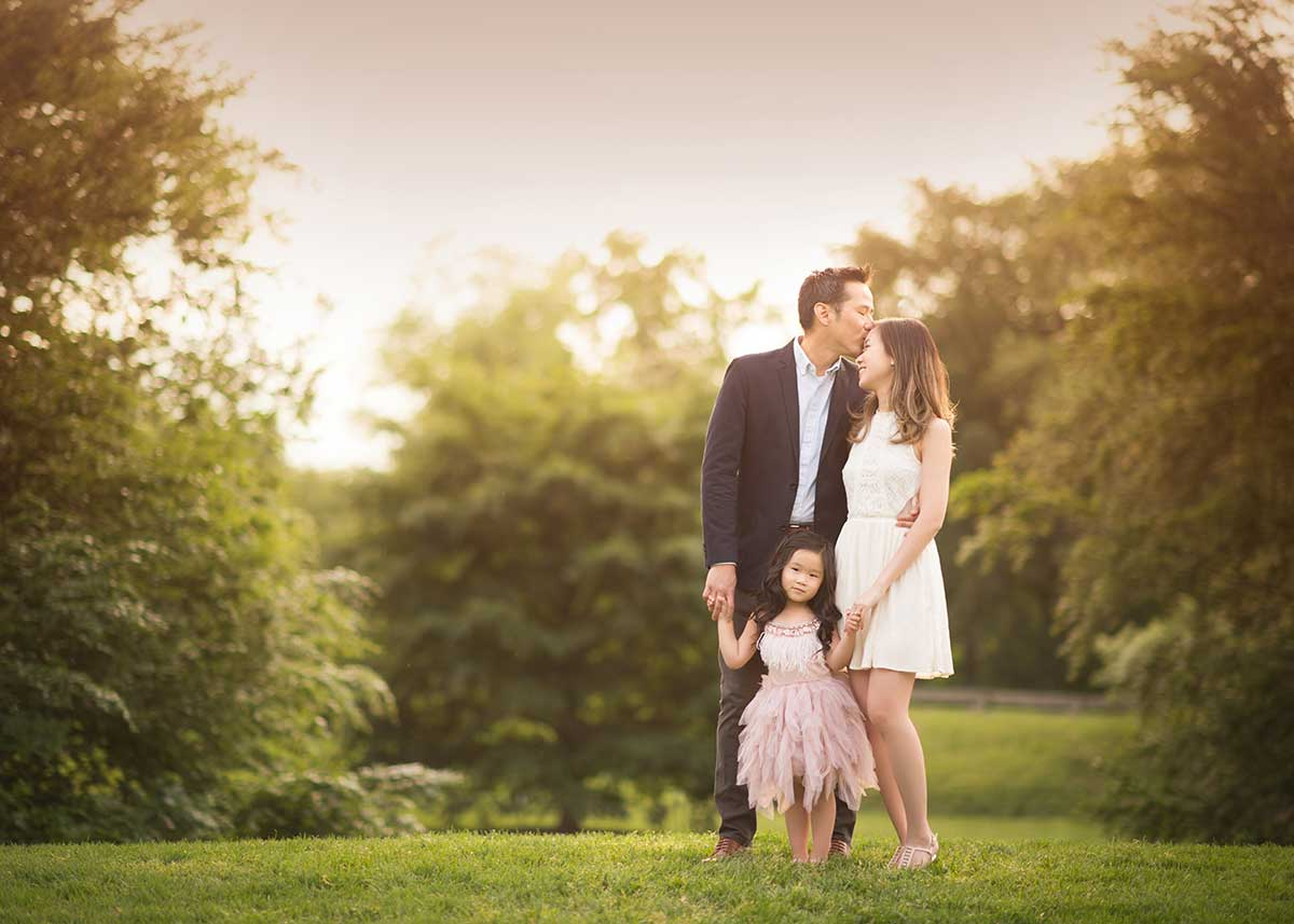 A kissing portrait of a family and their young daughter in Central Park