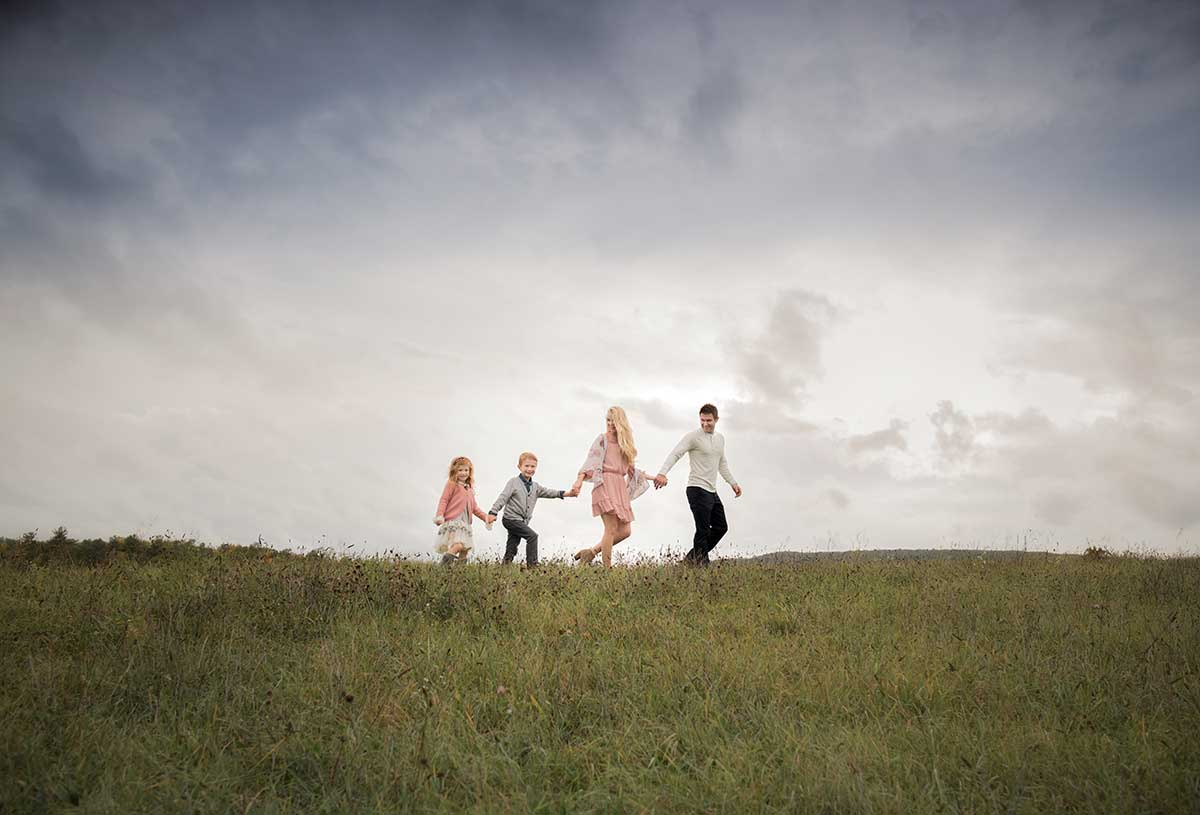 Family walking through a grass field