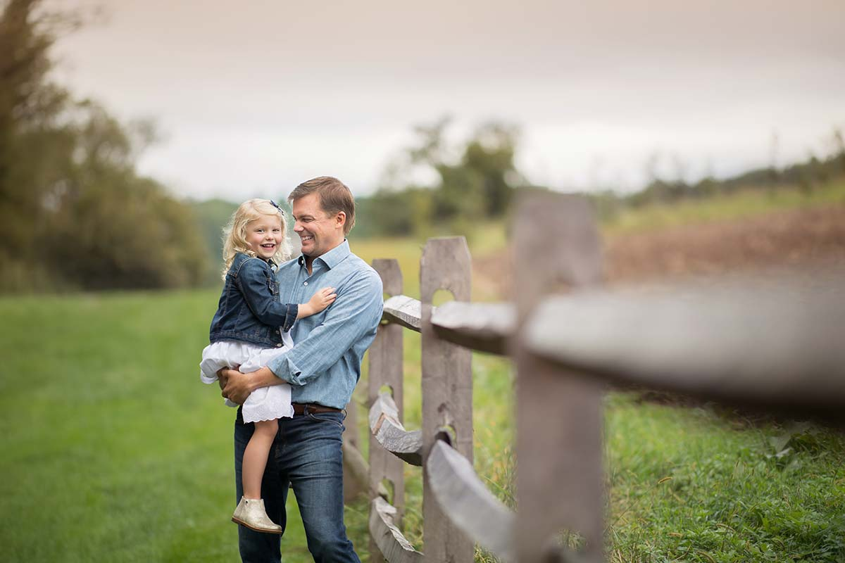 Father holding his daughter while leaning on a farm fence
