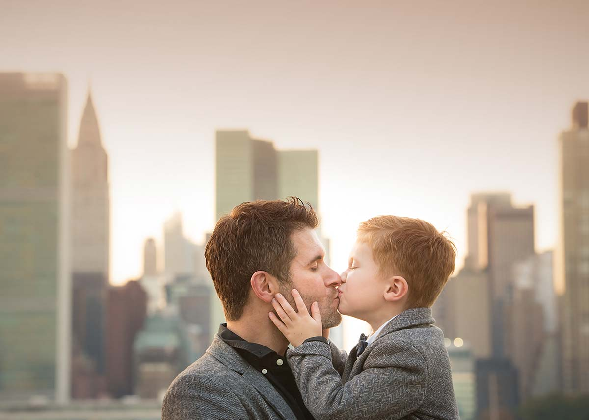 Father kissing his son with NYC skyline in the background