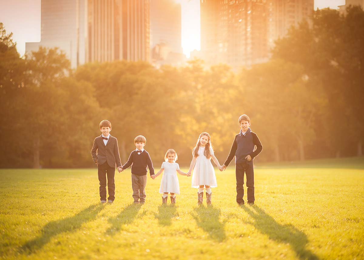 Five siblings dressed stylishly holding hands during sunset in Central Park NYC