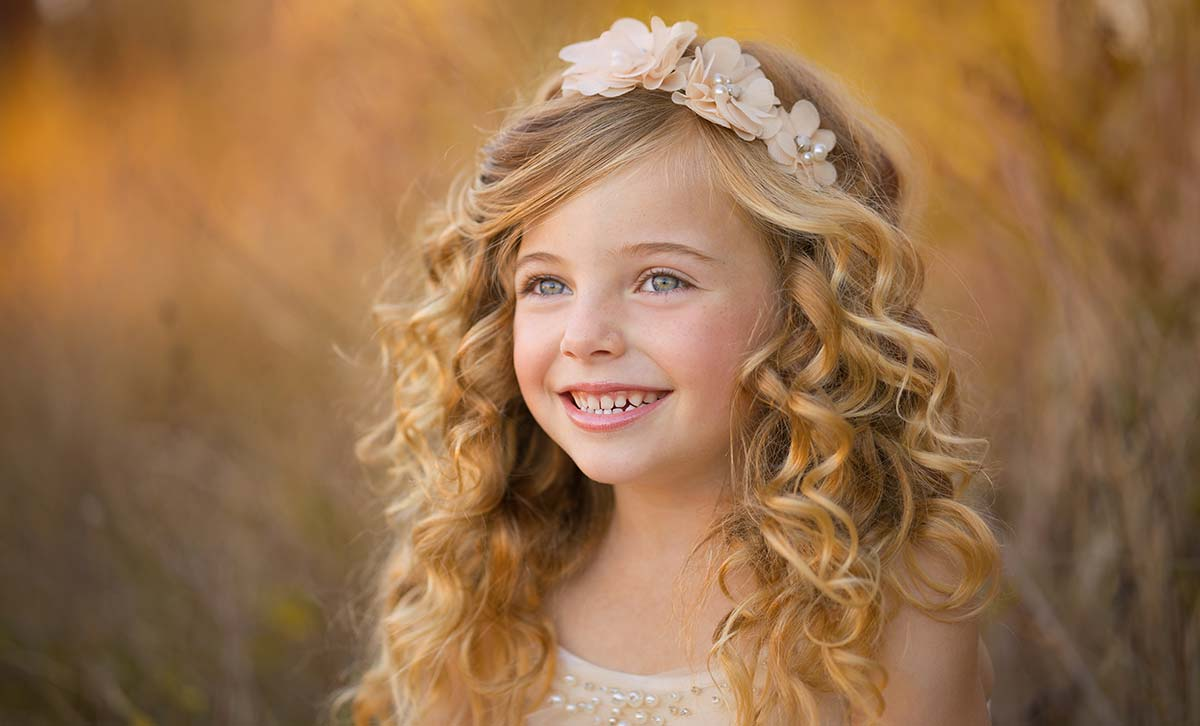 Pretty girl with curly blonde hair and headband smiling