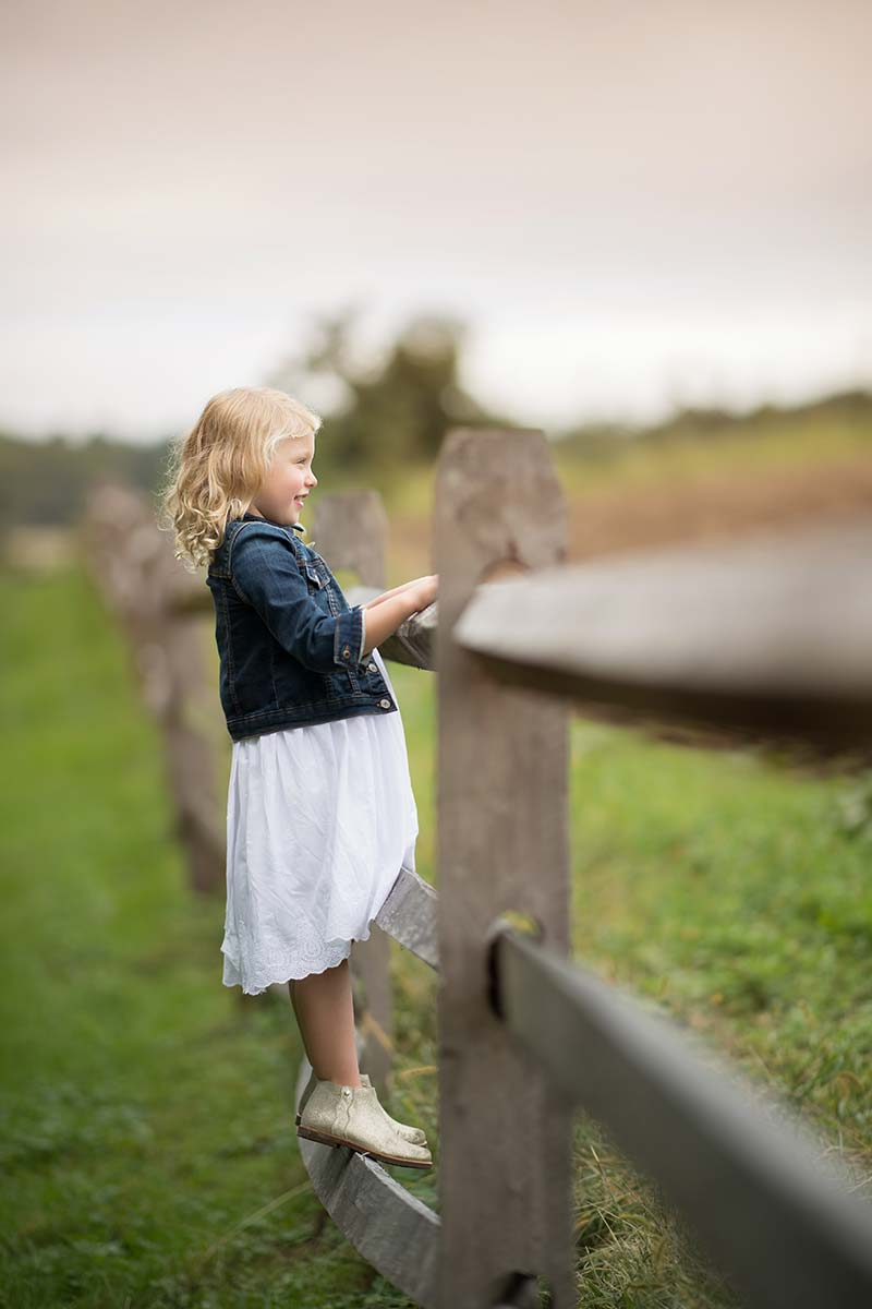 Young girl in a denim vest standing on a farm fence