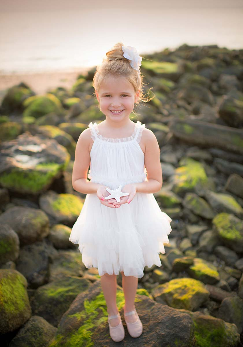 Girl in a white tutu posing on rocks at a beach